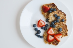 Brown pancakes from whole grain oats served with fresh bluberry and sliced strawberry on white background. Healthy dessert